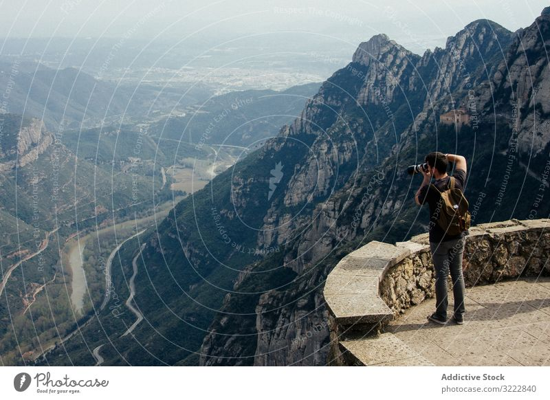Man photographing landscape from observation deck man taking photo range viewpoint barcelona spain breathtaking ridge travel serene nature photography tourism