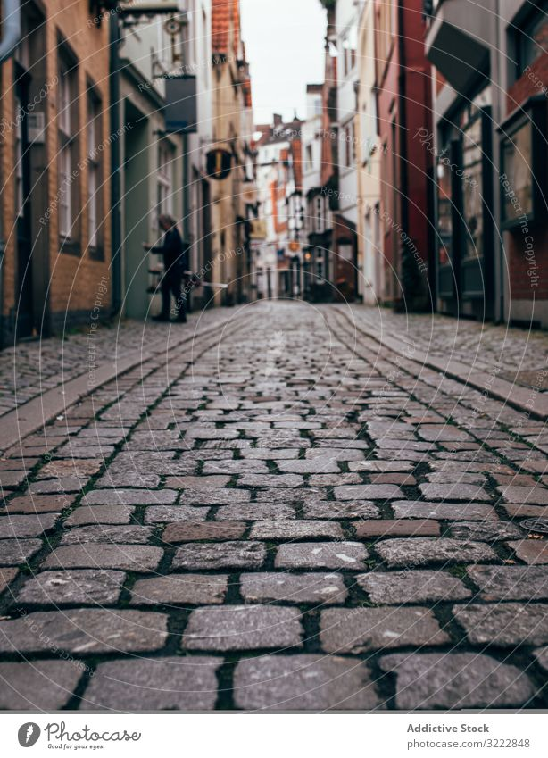 Narrow stone pavement street with houses in city cobblestone architecture town narrow building perspective exterior urban traditional footpath sidewalk