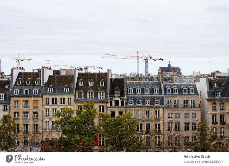 View of typical European buildings architecture house exterior mansard site contrast modern residential europe grey skyline city old town close roof cranes