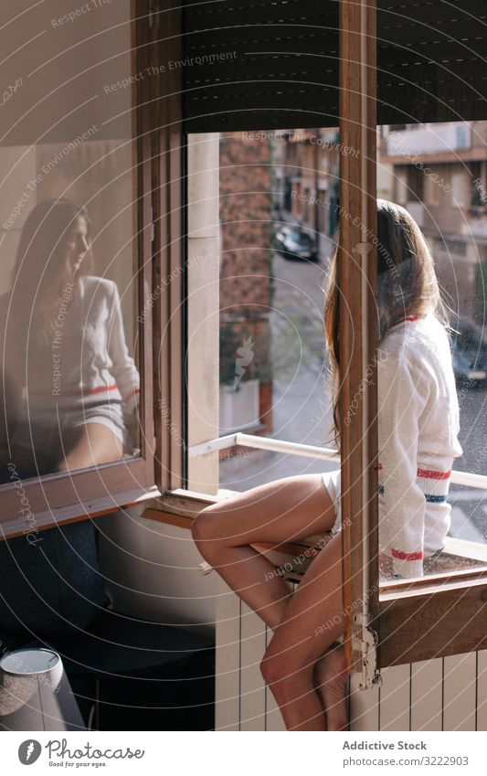 Woman sitting on window sill woman pensive tender thoughtful home calm sensual attractive female apartment casual young beautiful pretty upset morning relax