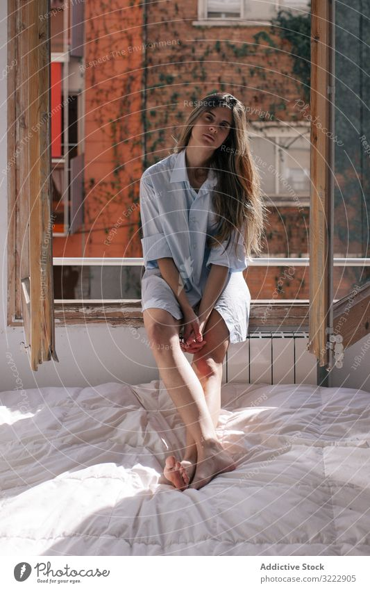 Woman sitting on window sill woman pensive bed tender bedroom thoughtful home calm sensual attractive female apartment casual young beautiful pretty upset