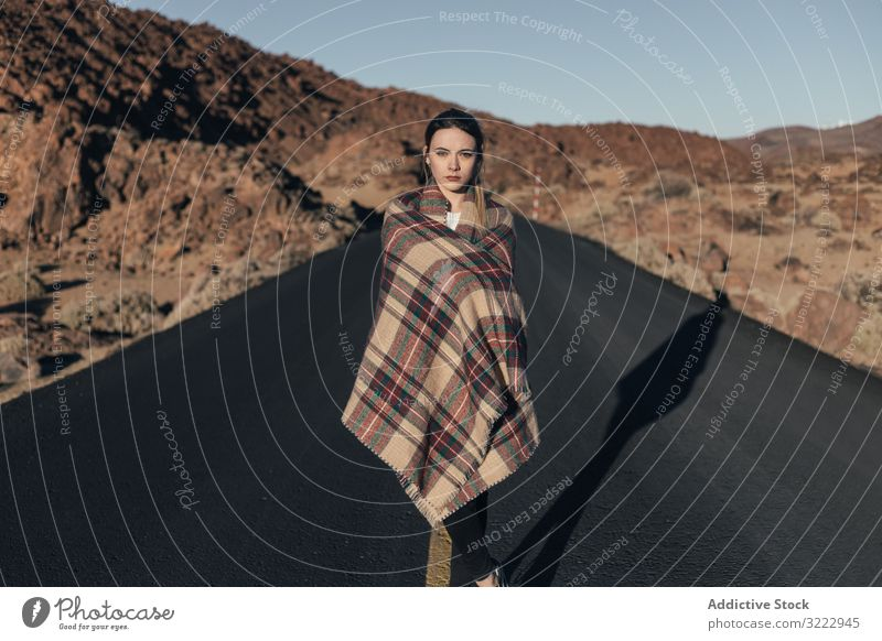 Traveler wearing blanket in sun during road trip woman mountains tenerife dream traveler bask young plaid female attractive cold wrapped cozy stand hill spain