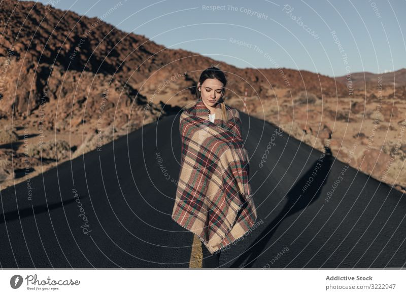 Traveler basking in sun during road trip woman mountains tenerife dream traveler young plaid female attractive cold wrapped cozy stand blanket hill spain