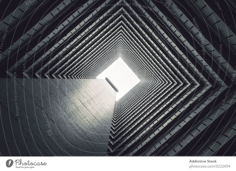 Dark courtyard of contemporary building architecture highrise tunnel dark closure perspective abstract shape residential strict construction square spain