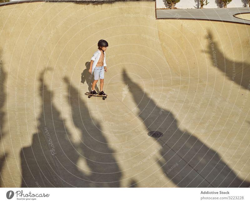 Child in helmet riding skateboard child skatepark ramp ride sunlight sport leisure hobby boy young wear childhood summer sunny active fun style urban lifestyle