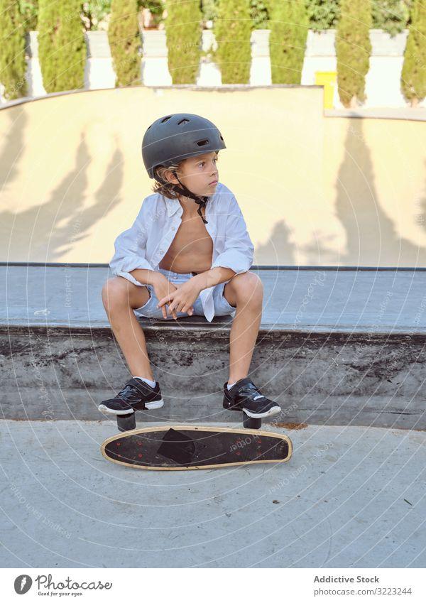 Boy with skateboard sitting on ramp boy skatepark helmet lifestyle sport leisure hobby male young childhood summer sunny careful active fun urban extreme