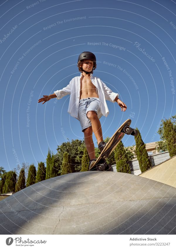 Child on ramp ready to show skateboard trick child skatepark ride sport leisure hobby boy hands apart young scream carefree childhood summer sunny active fun