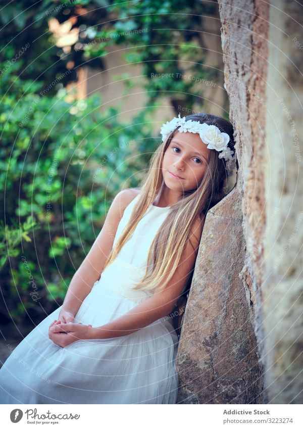 Little cute girl in white dress and flower headband child beautiful little adorable kid innocence pensive female purity individuality comely sweet hair positive