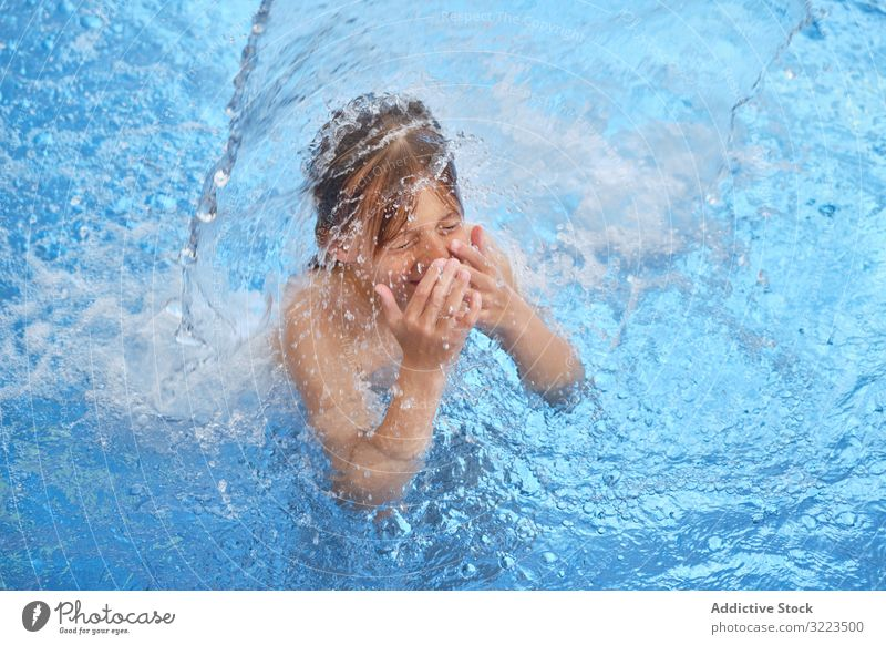 Young boy in blue water swimming pool young child float gasp for air closed eyes open mouth waterfall waterpark activity fun joy health leisure lifestyle