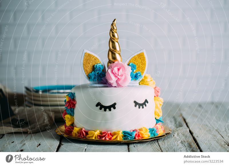 Cute unicorn cake with painted closed eyes sweet tasty birthday bright table appetizing holiday decoration gourmet yummy childhood event festive funny cooking