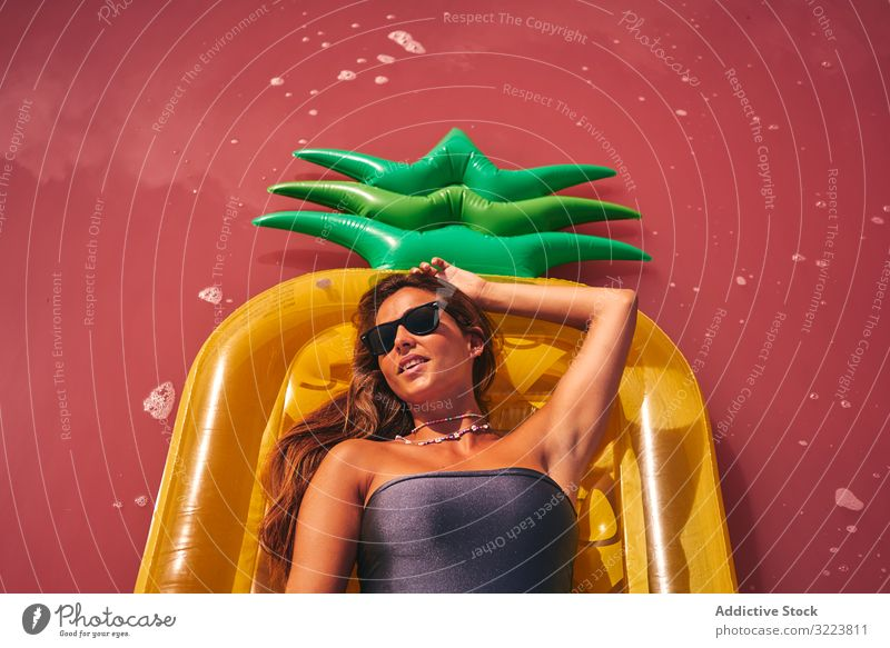 Dreamy female resting on inflatable mattress woman chill lying summer air mattress dreamy pink luxury appealing sunglasses swimwear red lagoon vivid creative