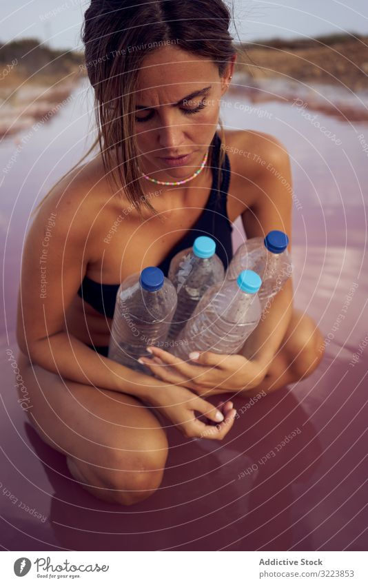 Concerned female in swimsuit collecting trash in natural lake pollution water contamination woman concerned pool pick bottle plastic red lagoon planet safety