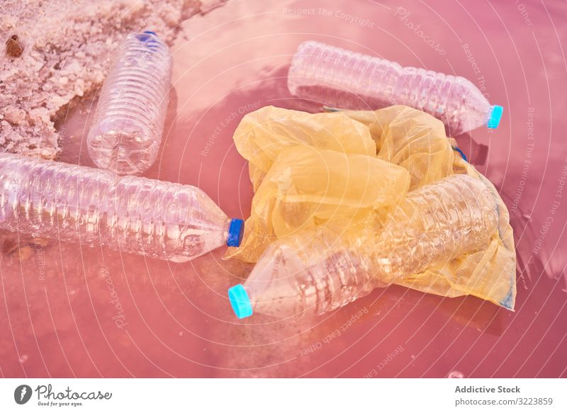 Plastic rubbish in polluted sea water plastic pollution bottle bag formation float shore red lagoon environment trash problem pink mineral salt messy natural