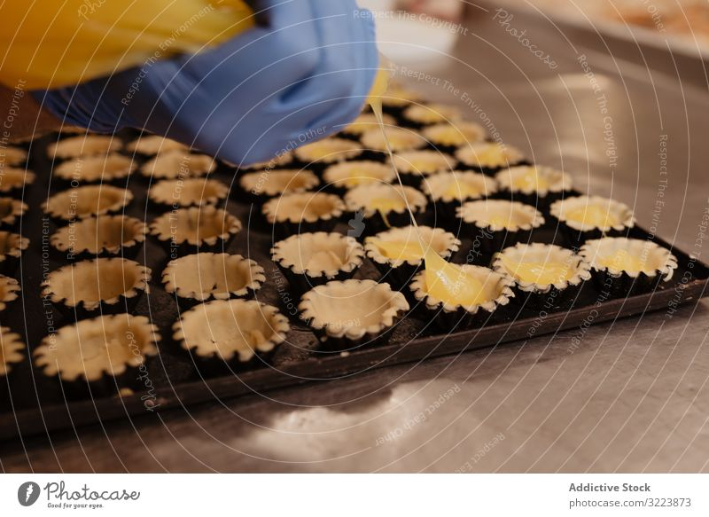 Crop baker squeezing dough on tray confectioner bakery squeeze cookie work kitchen preparation professional cuisine food paper pastry restaurant sweet chef