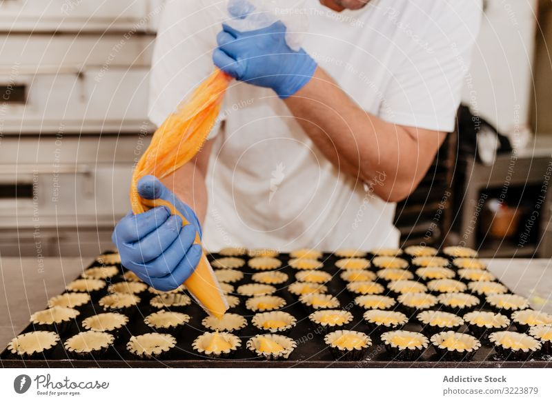 Crop baker filling pastry cases with jelly confectioner bakery squeeze tart bag kitchen sweet cuisine food dessert culinary tasty delicious yummy jam glove