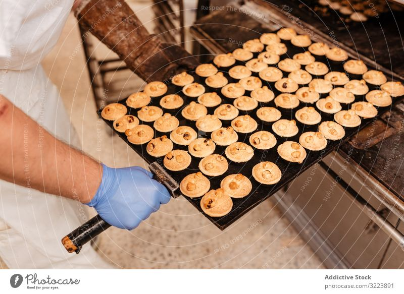 Bald baker checking pastry inside oven man bakery peek work confectioner cook hot process male adult uniform cuisine small business wait heat warm equipment