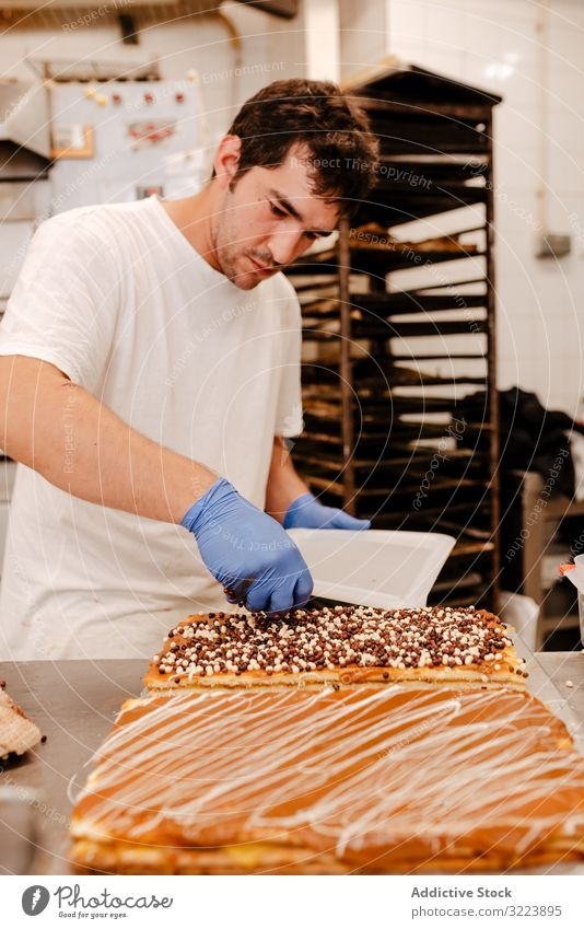 Anonymous baker spreading sprinkles on pastry confectioner bakery decor table quality cake preparation small business fresh occupation traditional work job
