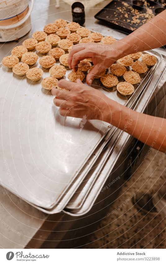 Crop baker arranging patisserie on tray confectioner bakery pastry arrange work cook quality food traditional preparation small business occupation busy job set