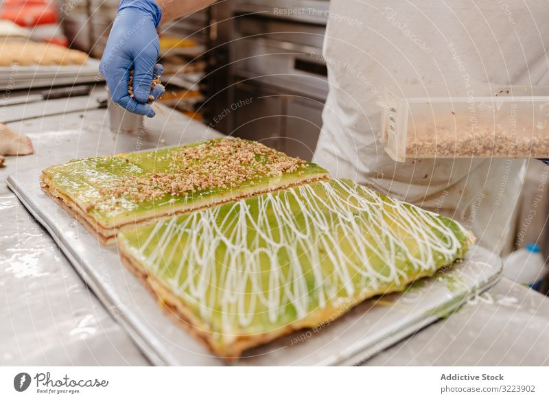 Crop baker spilling crumbs on cake confectioner bakery decor table kitchen pastry preparation small business work job fresh food quality occupation glove sweet