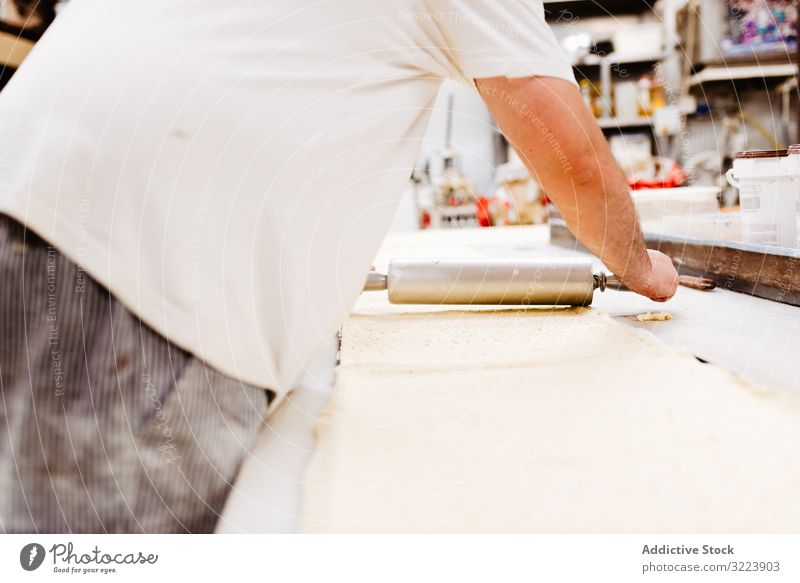 Crop cook rolling pastry dough confectioner bakery table kitchen work fresh small business professional cuisine raw overweight man chef job process preparation