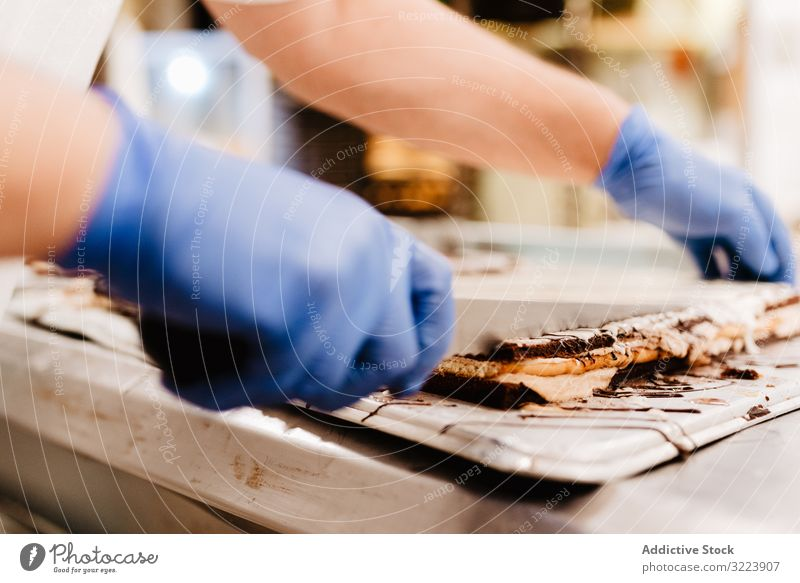 Crop confectioner cutting cake bakery table kitchen work pastry fresh knife layer glove small business food quality preparation traditional sweet calorie sugar