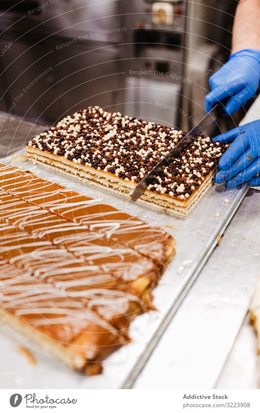 Anonymous cook cutting cake on table confectioner bakery knife pastry sweet fresh kitchen food preparation small business man uniform glove quality dessert