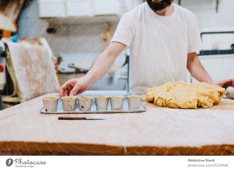 Bearded confectioner putting dough into cup bakery table kitchen pastry preparation fresh man raw cuisine professional food chef restaurant cafe cook recipe