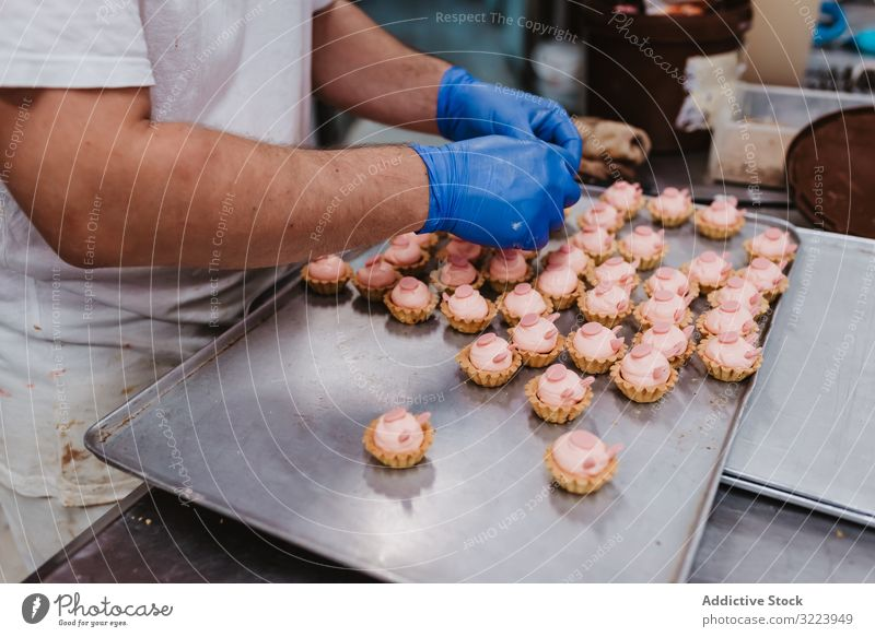 Anonymous baker decorating small cakes confectioner bakery pastry work quality food traditional man preparation production small business occupation patisserie