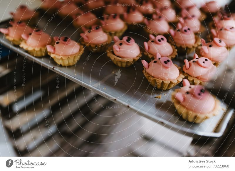 Tray with pig shaped desserts in bakery pastry rack tray symbol small pink cake ear snout food sweet fresh small business event preparation decor patisserie