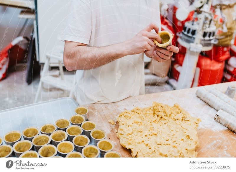 Crop cook decorating pastry with nuts confectioner bakery work cake quality food traditional man preparation production small business occupation patisserie