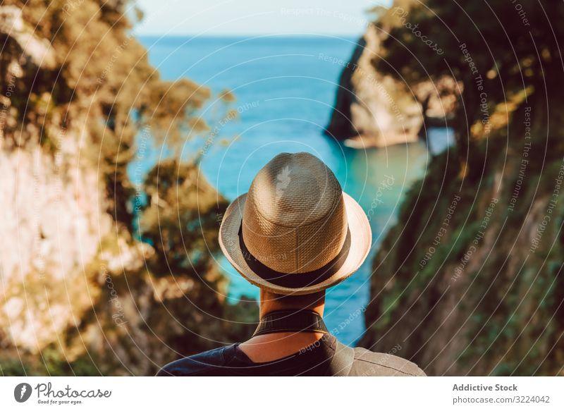 Female tourist contemplating picturesque landscape woman travel sea rock ribadedeva asturias spain trip vacation destination female casual hat stand enjoy