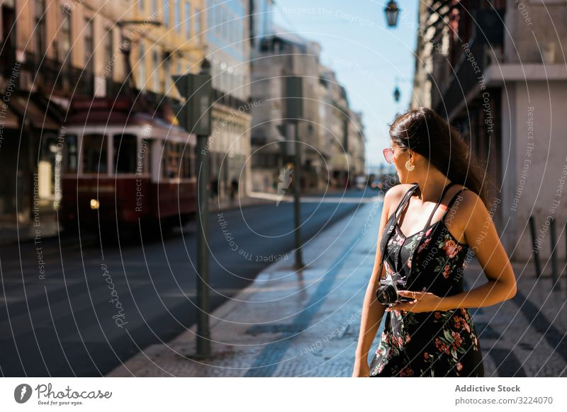 Woman holding a camera while standing on street woman town travel casual confident picture scenic lisbon portugal sunny city photographer young taking photo