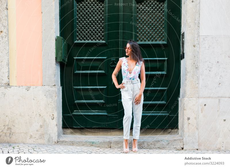 Confident stylish woman in sunglasses standing on city street modern trendy beautiful building confident scenic portugal lisbon young adult fashionable style