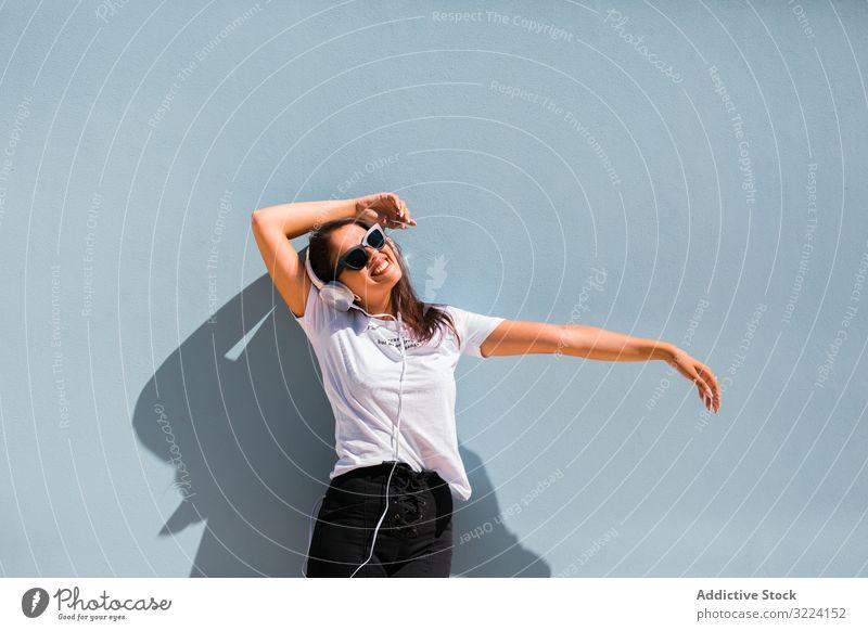 Cheerful casual woman in sunglasses standing on city street headphones stylish cheerful trendy millennial beautiful gadget music earphones device generation