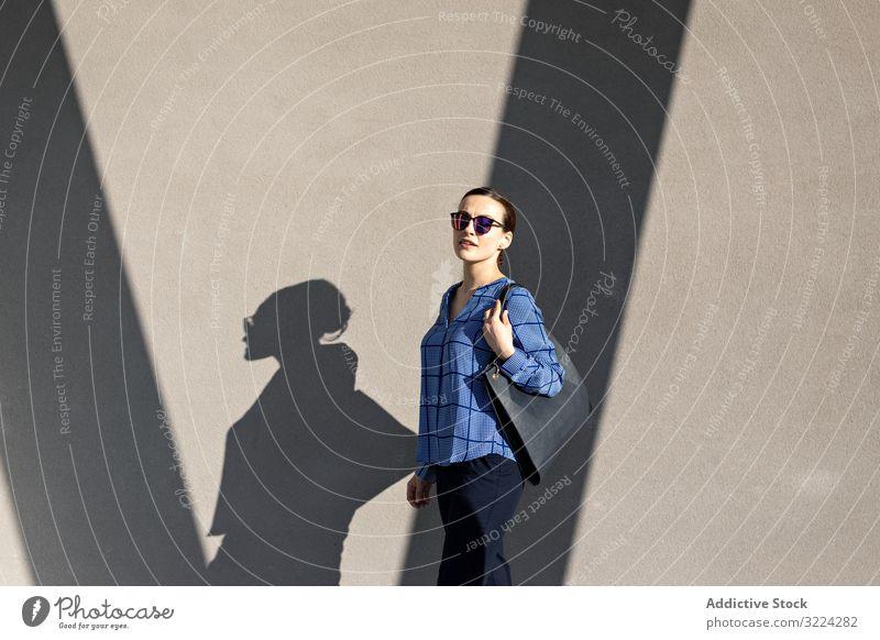 Smiling businesswoman standing near gray wall street smile city building pavement elegant modern urban female manager entrepreneur career bag sunglasses shades