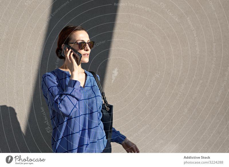 Businesswoman having smartphone conversation near gray wall businesswoman street talk building modern city urban female communication work job mobile device