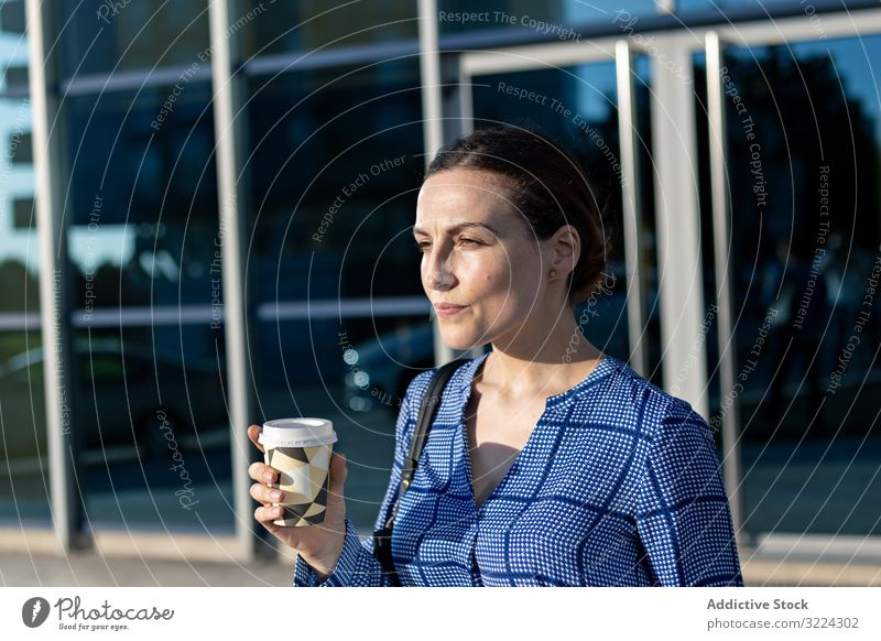 Businesswoman drinking on city street businesswoman building modern coffee to go elegant female serious beverage tea hot takeaway cup contemporary town