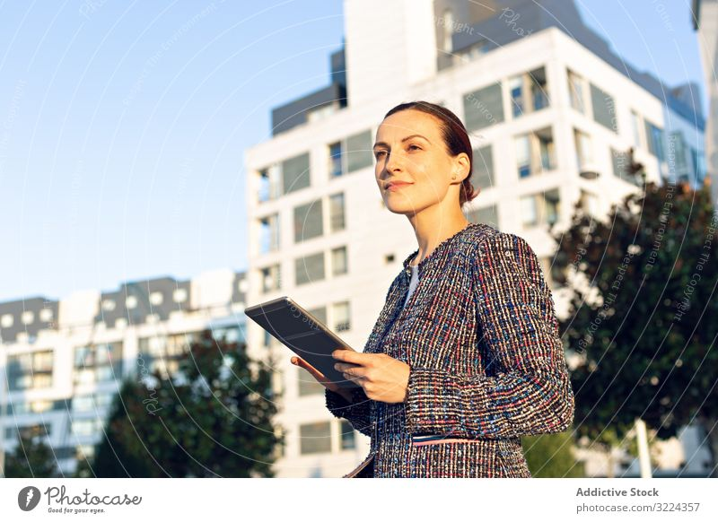 Confident entrepreneur with tablet on city street businesswoman using building serious confident sunny daytime female urban work job internet device gadget lady