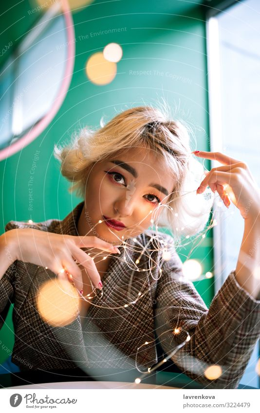Blond asian young woman with fairy string lights Festive Gold Joy Feasts & Celebrations Public Holiday Leisure and hobbies Hold Young woman Asians Blonde
