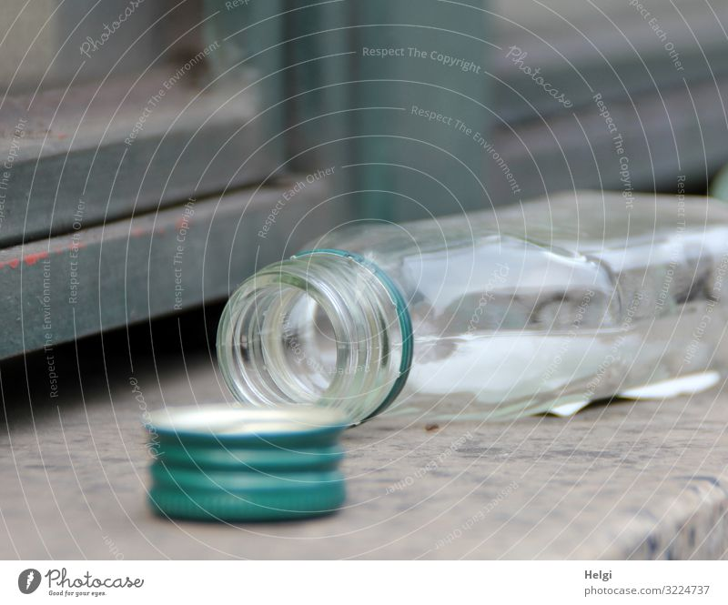 empty opened alcohol bottle lies on a wall Wall (barrier) Wall (building) Bottle Closure Cap Lie Authentic Small Gray Green Emotions Distress Lack of inhibition
