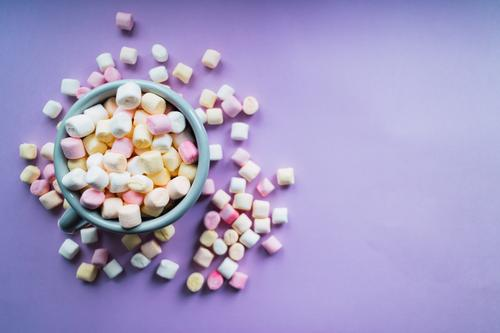 Hot chocolate with colorful marshmallows on purple background. Dessert Beverage Winter Decoration Soft Yellow Pink White Colour Sugar cup mug sweet Snack fluffy