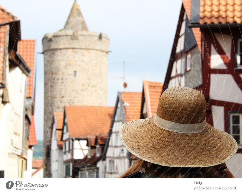 Lady with sun hat walks in an old town with half-timbered houses and historical tower Human being Adults 1 as field Town Old town House (Residential Structure)
