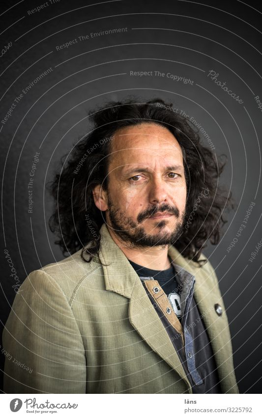 Portrait Human being Masculine Man Adults 1 45 - 60 years Chemnitz Wall (barrier) Wall (building) Jacket Black-haired Long-haired Observe Think Looking