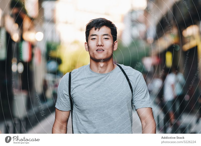 Confident Asian man walking along city street confident content casual t shirt handsome urban stroll modern summer asian ethnic young adult town relaxed