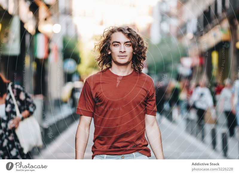 Dreamy modern man walking along city street dreamy casual t shirt handsome urban pensive stroll summer asian ethnic young adult town relaxed determined