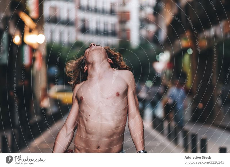 Sensual man and dancing shirtless on street sensual gaze confident pensive naked stand handsome urban long hair young adult day desire passion sexual body torso