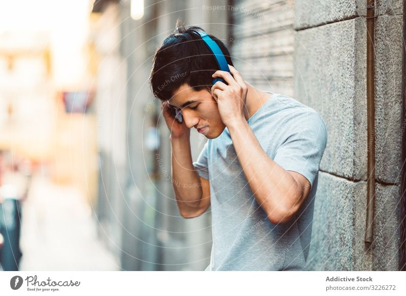 Man in headphones listening music on the street man city using streaming content cool joyful modern casual stand sunny town young adult internet online