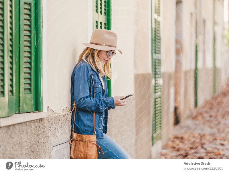 Woman with smartphone leaning on stone house woman happy beautiful talking attractive charming relaxation street female confident model communication thoughtful