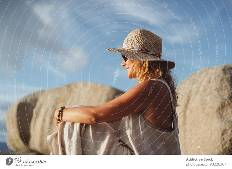 Carefree lady enjoying rest on coast near cliffs woman carefree travel optimistic seaside happy smile hat trip vacation gorgeous sunglasses recreation cheerful
