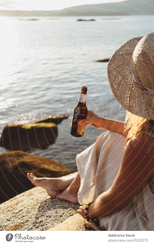 Woman relaxing and drinking beer at beach woman coast seaside lounge refreshment chill sunlight enjoy solitude bottle travel alcohol holidays trip vacation
